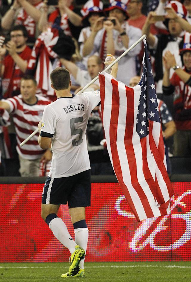 U.S. defender Matt Besler carries a U.S. flag and gestures to fans after his team's to win over 2-0 Jamaica in a World Cup qualifier soccer match at Sporting Park in Kansas City, Kan., Friday, Oct. 11, 2013. (AP Photo/Colin E. Braley)