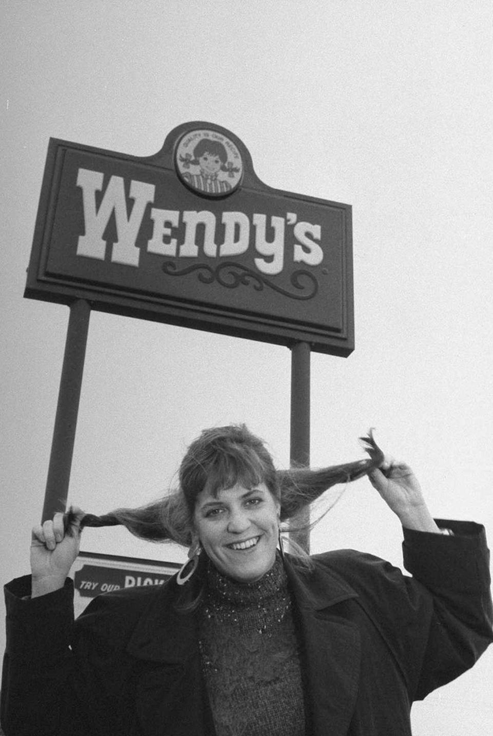 <p>You may recognize Wendy Morse because she is <em>the</em> Wendy, even depicted in the chain's illustrative logo. Daughter of Founder Dave Thomas, she's seen here posing in front of the sign in 1989.</p>