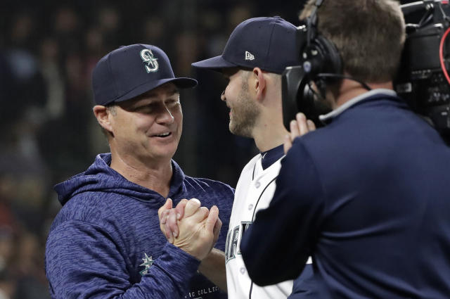 Seattle Mariners manager Scott Servais, left, greets starting pitcher James Paxton, center, Saturday, May 19, 2018, in Seattle after Paxton threw a three-hitter against the Detroit Tigers as the Mariners won the baseball game 7-2. (AP Photo/Ted S. Warren)