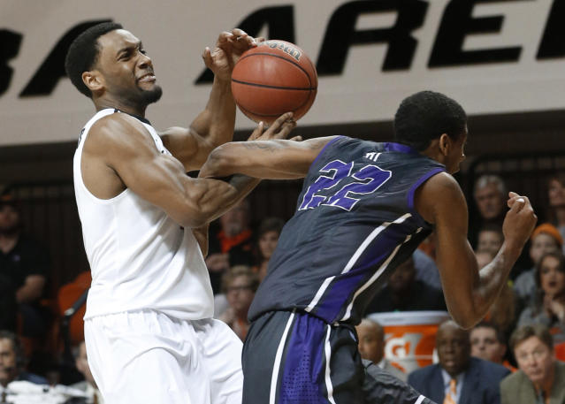Oklahoma State wing Brian Williams (4) is fouled by TCU guard Jarvis Ray (22) during the second half of an NCAA college basketball game in Stillwater, Okla., Wednesday, Jan. 15, 2014. Oklahoma State won 82-50. (AP Photo/Sue Ogrocki)