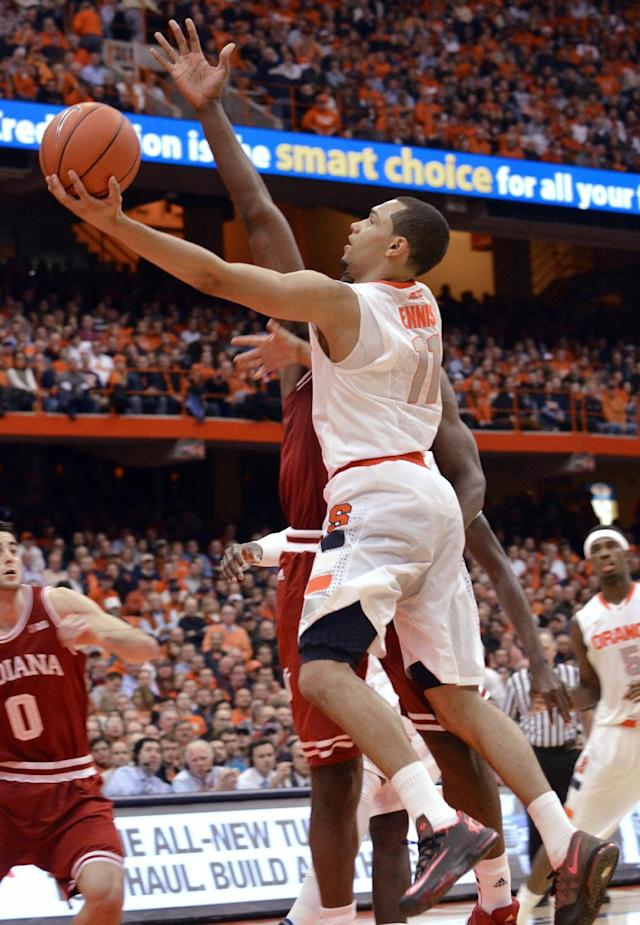 Syracuse's Tyler Ennis (11) draws a foul against Indiana's Noah Vonleh while driving to the basket during the second half of an NCAA college basketball game in Syracuse, N.Y., Tuesday, Dec. 3, 2013. Syracuse won 69-52. (AP Photo/Kevin Rivoli)