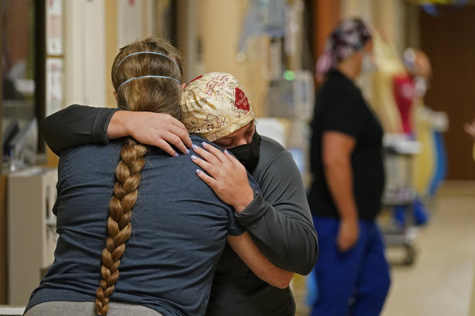 ICU nurse Melinda Hunt, facing, hugs the sister of a COVID-19 patient she had been caring for, who had just passed away, inside a COVID unit at the Willis-Knighton Medical Center in Shreveport, La., Wednesday, Aug. 18, 2021. (AP Photo/Gerald Herbert)