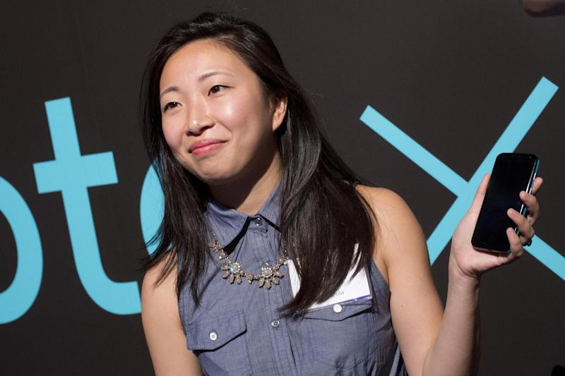 Cathay Bi, a product marketing manager with Motorola, shows the Moto X smartphone, Thursday, Aug. 1, 2013 at a press preview in New York. (AP Photo/Mark Lennihan)