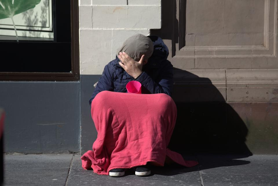 Beggar Hiding Face While Sitting On Sidewalk By Building