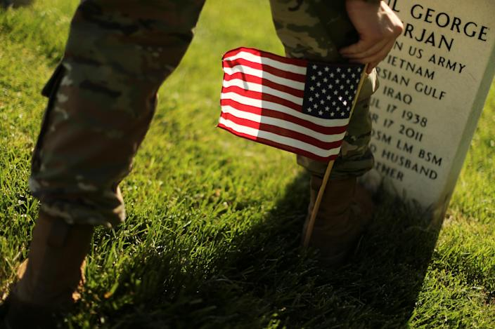 <p>A U.S. Army soldier of the 3rd United States Infantry Regiment uses his boot to measure where to place U.S. flags on graves at Arlington National Cemetery in advance of Memorial Day in Arlington, Va., May 24, 2018. (Photo: Jonathan Ernst/Reuters) </p>