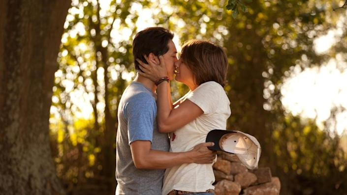 a photo of The Walking Dead characters Glenn and Maggie standing under a tree and kissing in Season 2