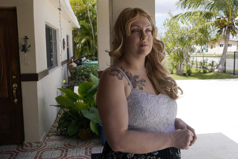 """Nicole Russell looks out from her porch, Friday, March 12, 2021, in Kendall, Fla. Because of the pandemic, Nicole because fearful of leaving her home and retreated to her bedroom for days at a time. While some felt restricted by the confinement of home """"caves"""", others found a sense of safety and comfort, becoming increasingly accustomed to the isolation. (AP Photo/Marta Lavandier)"""