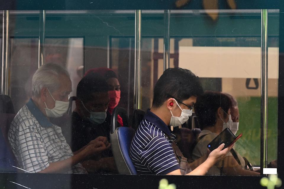 People wearing protective facemasks travel on a public bus in Singapore on September 14, 2021. (Photo by Roslan RAHMAN / AFP) (Photo by ROSLAN RAHMAN/AFP via Getty Images)