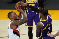 Los Angeles Lakers guard Kentavious Caldwell-Pope (1) blocks a shot by Portland Trail Blazers guard Damian Lillard (0) during the first half of an NBA basketball game Friday, Feb. 26, 2021, in Los Angeles. (AP Photo/Mark J. Terrill)