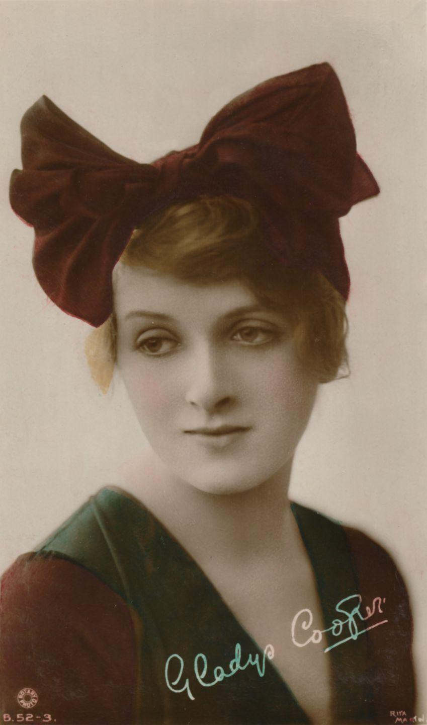 """<p>Another postcard from her modeling days, Cooper looks ultra-chic with her short hair wrapped in this oversized red bow. The actress often returned to the camera for photo shoots, even when she no longer needed the money, and she was a favorite """"pinup"""" of British soldiers in WWI. </p>"""