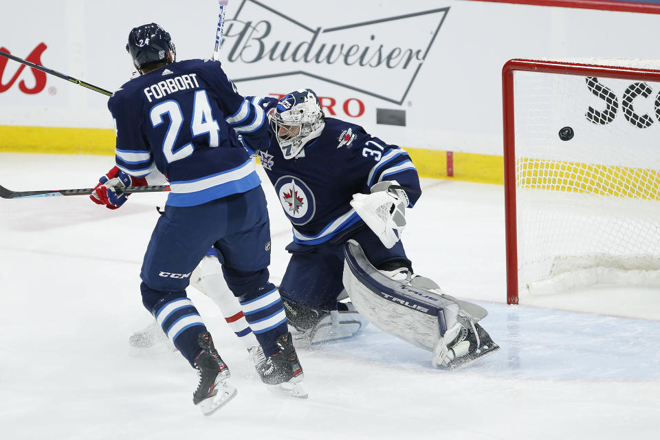 A deflection by Montreal Canadiens' Brendan Gallagher, not seen, goes off the crossbar behind Winnipeg Jets goaltender Connor Hellebuyck (37) as Derek Forbort (24) defends during the first period of an NHL hockey game Saturday, Feb. 27, 2021, in Winnipeg, Manitoba. (John Woods/The Canadian Press via AP)