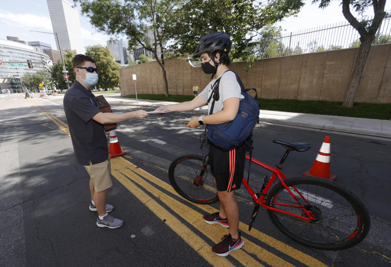 Election judge John Seward, left, hands a ballot to Nicholas Garza as voters pick up—and drop off—their ballots at a drive-thru location outside the Denver Election Commission building, Tuesday, June 30, 2020, in downtown Denver. (AP Photo/David Zalubowski)