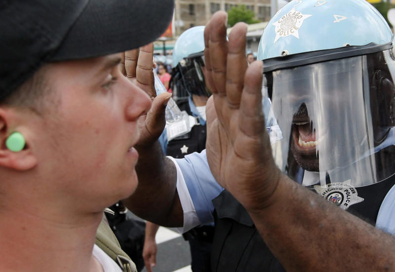 A Chicago Police officer confronts a protester during a march and rally at this weekend's NATO summit in Chicago Sunday, May 20, 2012 in Chicago. (AP Photo/Charles Rex Arbogast)
