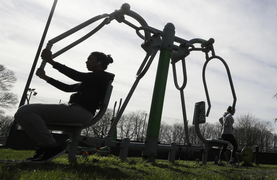 FILE - In this file photo dated Saturday, March 21, 2020, people use outdoor public gym equipment at a park after indoor gyms were asked to close by the government to help limit the spread of coronavirus in London. The British government insists that science is guiding its decisions as the country navigates its way through the coronavirus pandemic. But a self-appointed group of independent experts led by a former government chief adviser says it sees little evidence-based about Britain's response. Unlike other countries, the scientific opposition to Britain's approach is remarkably organized. The independent group sits almost in parallel to the government's own scientists, assesses the same outbreak indicators and has put out detailed reports on issues such contact tracing, reopening schools and pubs, and relaxing social distancing (AP Photo/Kirsty Wigglesworth, FILE)