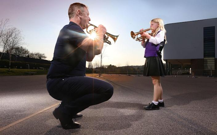 Guzelian Abigail James (9), playing cornet, a member of Bradford Youth Brass Band rehearses with her music teacher, Morgan Griffiths, for the first time in 13 months, at Titus Salt School in Baildon, West Yorkshire - Guzelian/Lorne Campbell