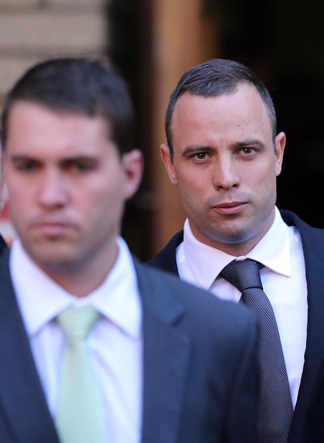Oscar Pistorius with unidentified relative leaves at the high court in Pretoria, South Africa, Wednesday, May 14, 2014. Pistorius is charged with murder for the shooting death of his girlfriend, Reeva Steenkamp, on Valentines Day in 2013. A judge ruled on Wednesday, that Pistorius be sent for psychiatric observation. (AP Photo/Themba Hadebe)