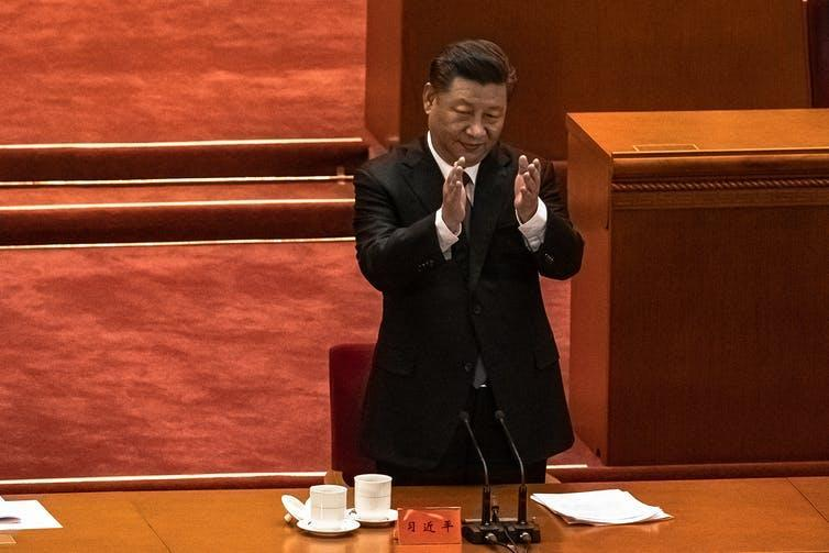 Xi Jinping applauding at a conference