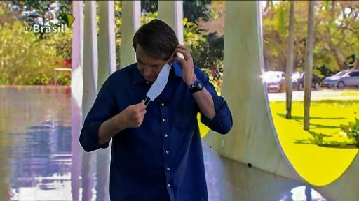 A screen grab from TV Brasil shows Brazilian President Jair Bolsonaro putting a face mask on as he prepares to speak with journalists at Planalto Palace in Brasilia on July 7, 2020. He later removed it