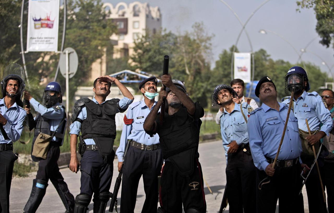 A Pakistani riot police officer, center, fires a tear gas canister toward protesters, during clashes that erupted as protestors tried to approach the U.S. embassy, in Islamabad, Pakistan, Friday, Sept. 21, 2012. Pakistani police opened fire on rioters who were torching a cinema during a protest against an anti-Islam film Friday, and security forces clashed with demonstrators in several other cities in Pakistan on a holiday declared by the government so people could rally against the video. Thousands of people protested in several other countries, some of them burning American flags and effigies of President Barack Obama. (AP Photo/Muhammed Muheisen)