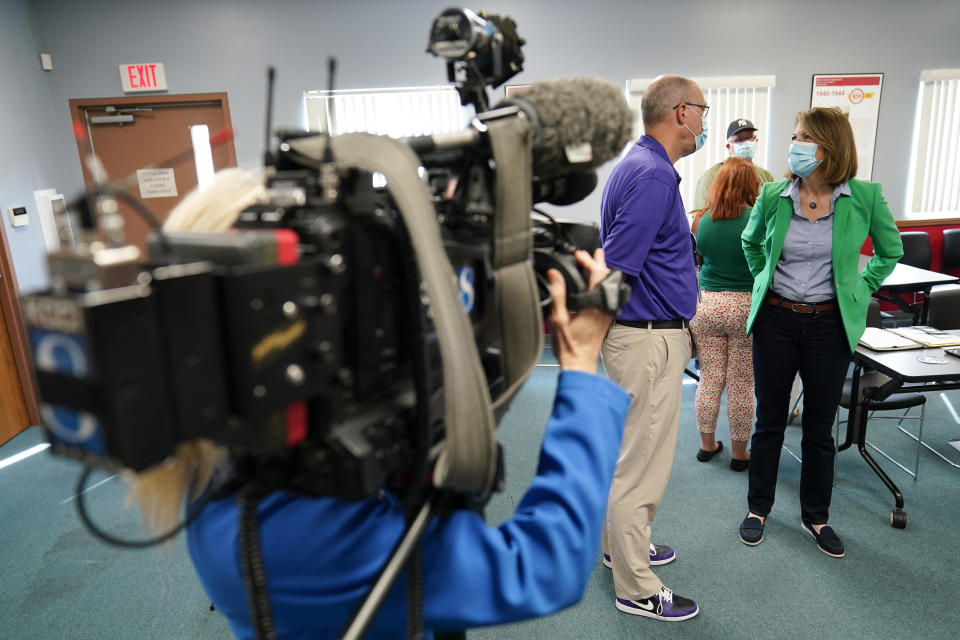 In this Sept. 2, 2021, photo Rep. Cindy Axne, D-Iowa, talks with D.T. Magee, of the Norwalk Community School District, during a meeting with local officials in Indianola, Iowa. (AP Photo/Charlie Neibergall)