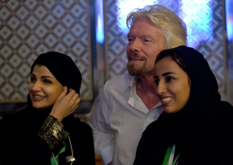 "Founder of Virgin group Sir Richard Branson poses with Saudi women during last year's ""Future Investment Initiative"" in Riyadh; Branson is another key personality to have withdrawn from this year's event"
