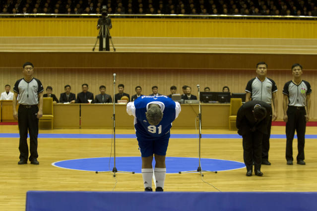 Dennis Rodman bows to North Korean leader Kim Jong Un, seated above in the stands, before an exhibition basketball game with U.S. and North Korean players at an indoor stadium in Pyongyang, North Korea on Wednesday, Jan. 8, 2014. (AP Photo/Kim Kwang Hyon)