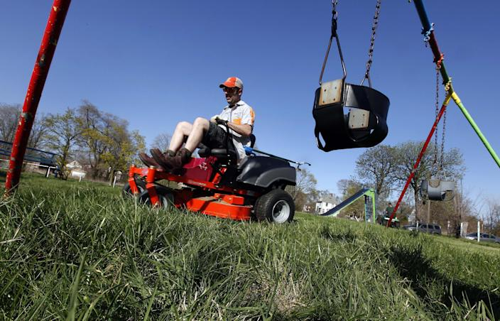 Mower gang member Tom Nadrone, of Birmingham mows at Duweke Park in Detroit, Wednesday May 1, 2013. The Mower Gang, a group of volunteer lawn mower riders, adopt parks beginning in the spring and keep them free of high-grass throughout the summer. (AP Photo/Paul Sancya)