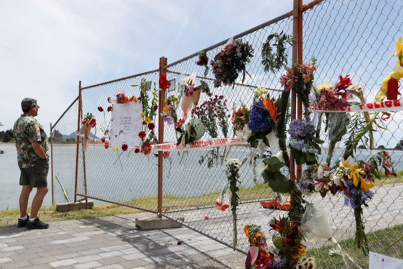 A man looks at a memorial at the harbour in Whakatane, following the White Island volcano eruption in New Zealand