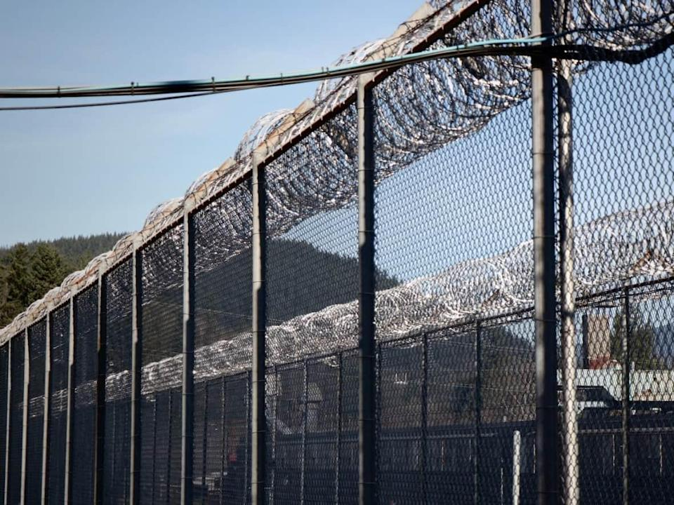 A file photo from 2018 shows barbed wire lining the fences surrounding the Mission Medium Security Institution in B.C.  (Rafferty Baker/CBC - image credit)