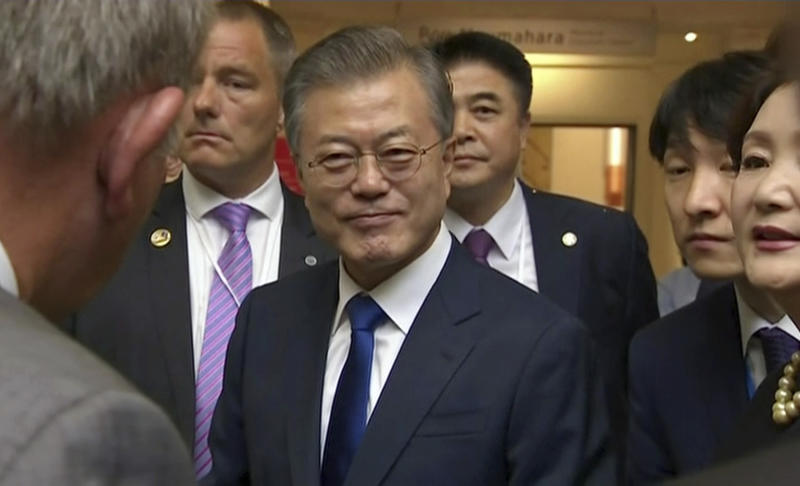 """In this image made from a video, South Korean President Moon Jae-in, center, prepares to leave after a wreath laying ceremony at the Auckland War Memorial Museum in Auckland, New Zealand Monday, Dec. 3, 2018. Moon says U.S. President Donald Trump told him he has a """"very friendly view"""" of North Korean leader Kim Jong Un and wants to grant his wishes if he denuclearizes. (TVNZ via AP)"""