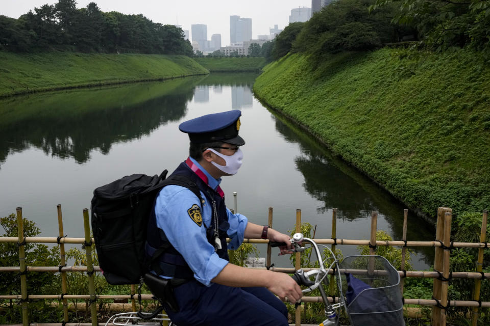 A police officer rides his bicycle along Imperial Palace Sunday, July 11, 2021, in Tokyo. The fourth state of emergency would go in effect on Monday and last through Aug. 22, despite the opening ceremony of Tokyo Olympics will be held in less than two weeks. (AP Photo/Kiichiro Sato)