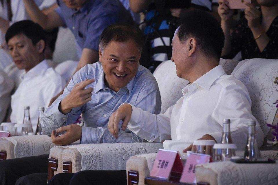 Zhang Li, co-chairman and co-founder of Guangzhou R&F Properties (centre) and Wang Jianlin, the chairman of Dalian Wanda Group (right), during a signing ceremony for the disposal of Wanda's assets in Beijing on July 19, 2017. Photo: AFP
