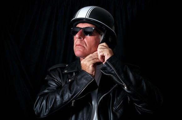 Man in leather jacket and sunglasses strapping on a helmet