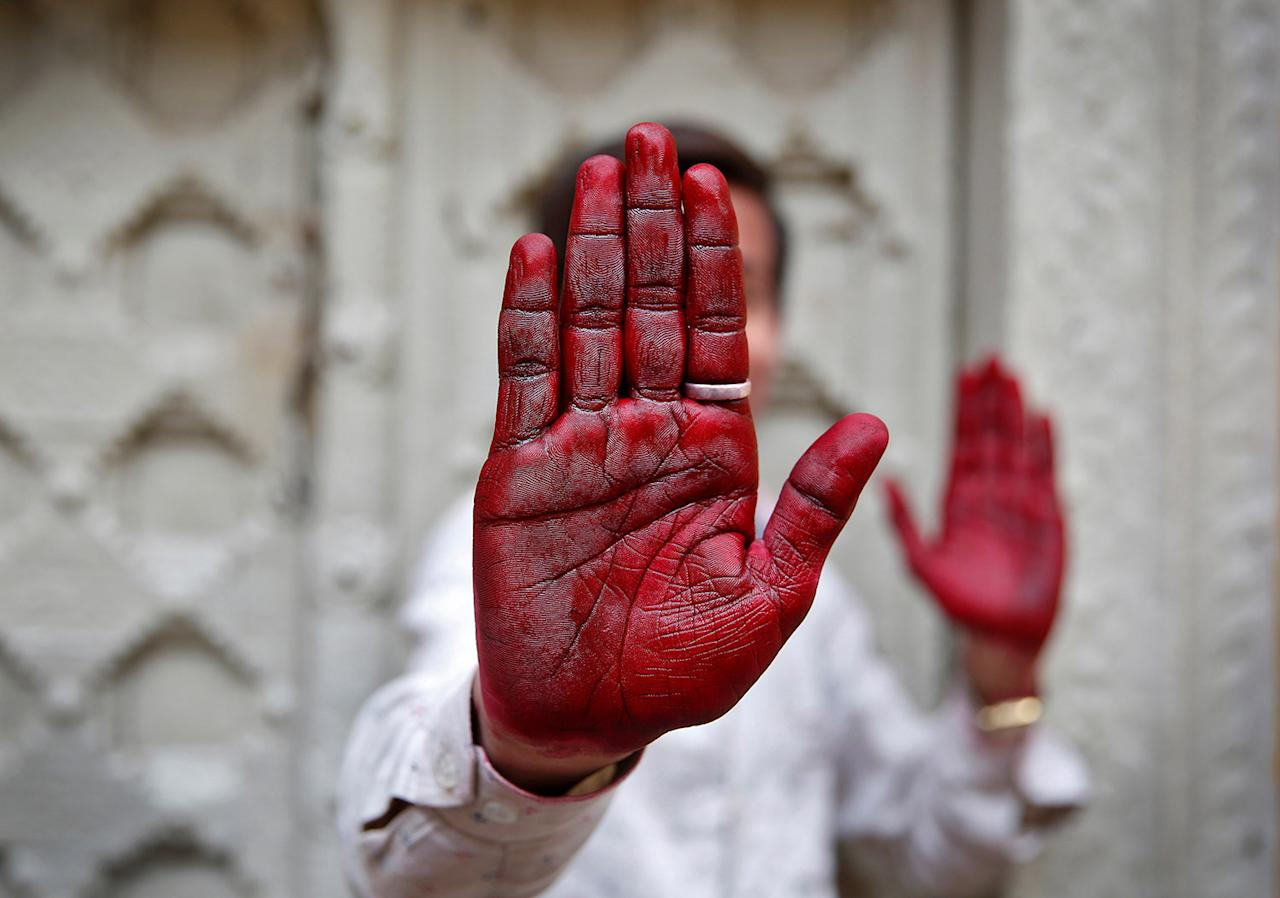 <p>A Hindu devotee displays his inked hand after taking part in the religious festival of Holi in Vrindavan, in the northern state of Uttar Pradesh, India, March 8, 2017. (Photo: Cathal McNaughton/Reuters) </p>