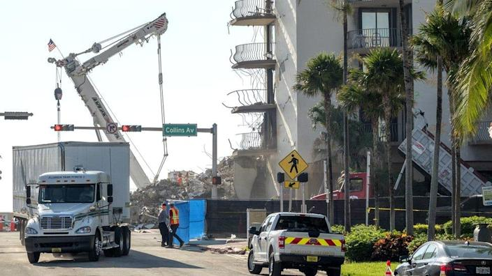 Workers clean the area of the partially collapsed Champlain Towers South condominium building in Surfside, Florida, 4 July 2021