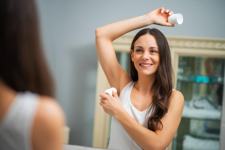 Portrait of young woman who is applying roller deodorant in her armpit. (Photo: Photodjo via Getty Images)