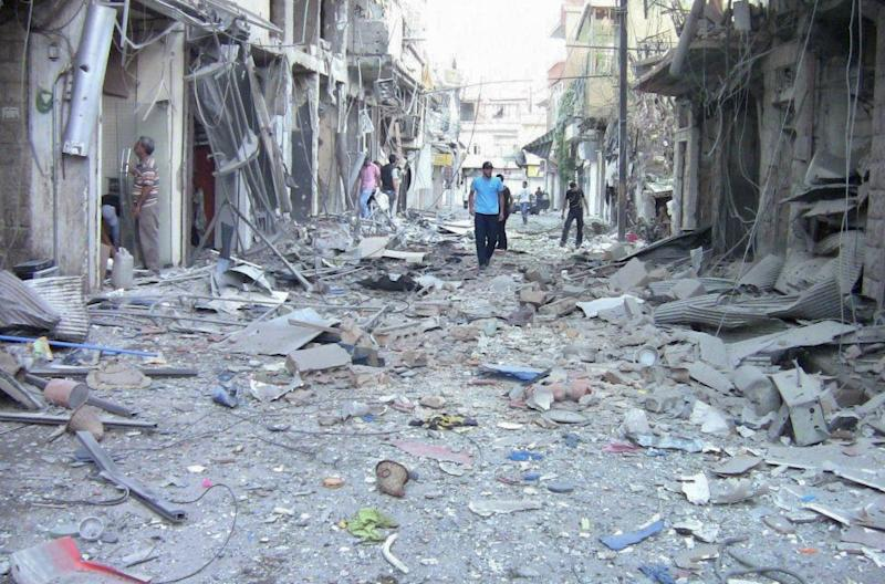 A picture released by the Syrian opposition's Shaam News Network on August 8, 2012, shows men inspecting damage allegedly caused by shelling by regime forces of a shopping district in Zabadani