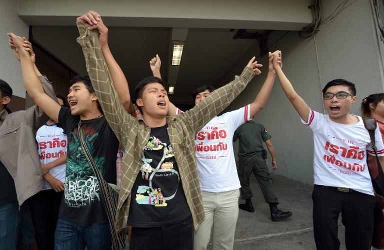 Local students and activists shout slogans after a court announced the verdict on two young Thais accused of insulting the monarchy in a university play, in Bangkok, on February 23, 2015