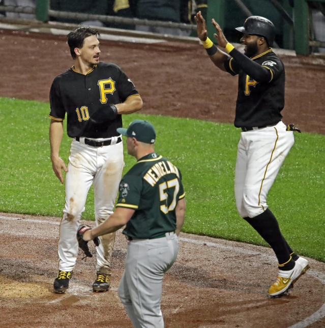 Pittsburgh Pirates' Gregory Polanco, right, and Bryan Reynolds (10) celebrate after scoring on a triple by Kevin Newman off Oakland Athletics relief pitcher J.B. Wendelken (57) during the seventh inning of a baseball game in Pittsburgh, Saturday, May 4, 2019. (AP Photo/Gene J. Puskar)