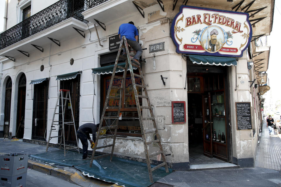 Men work on the facade of the El Federal Bar in Buenos Aires, Argentina, Tuesday, Nov. 10, 2020. Overall, about 2,000 bars, restaurants and cafes have closed in Argentina's capital since the lockdown caused by the new coronavirus pandemic. (AP Photo/Natacha Pisarenko)