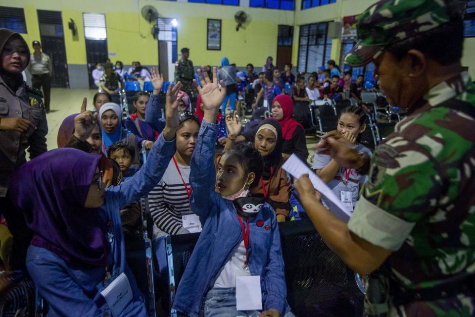 Indonesian women deported from Malaysia for working illegally, wait to be processed by Indonesian immigration officers at Nunukan, Indonesia, Thursday, Dec. 6, 2018. The porous border in Borneo, an island shared by Malaysia and Indonesia, serves as a corridor for opportunistic Indonesian workers, including women and young girls hoping to pull themselves out of poverty. Many go illegally, sometimes falsifying documents or lying about their age, leaving them vulnerable to exploitation. (AP Photo/Binsar Bakkara)