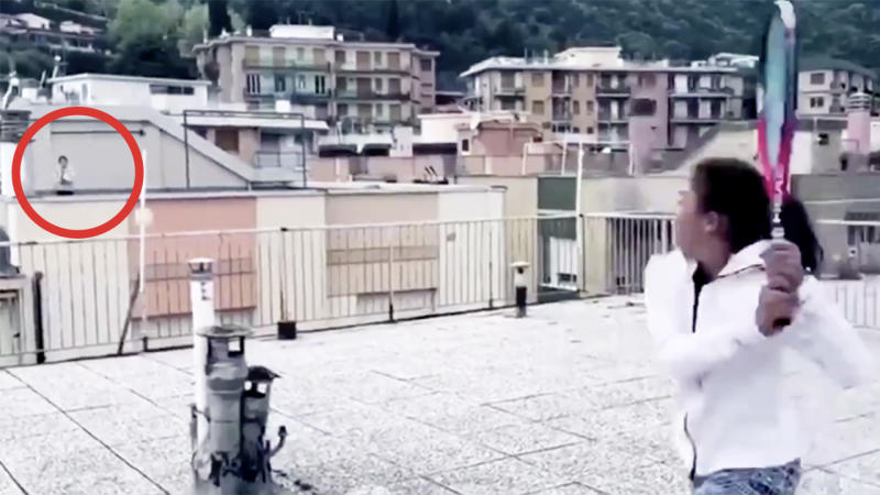 Young girls play social-distancing tennis on rooftop in Italy