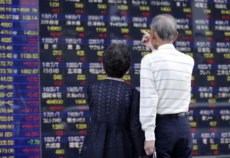 A couple watches the electronic stock board of a securities firm in Tokyo, Thursday, Sept. 19, 2013. The Nikkei 225 closed up 260.82 points, or 1.80 percent, at 14,766.18 Thursday as Asian stock markets surged after the U.S. Federal Reserve unexpectedly refrained from reducing its massive economic stimulus. (AP Photo/Shizuo Kambayashi)