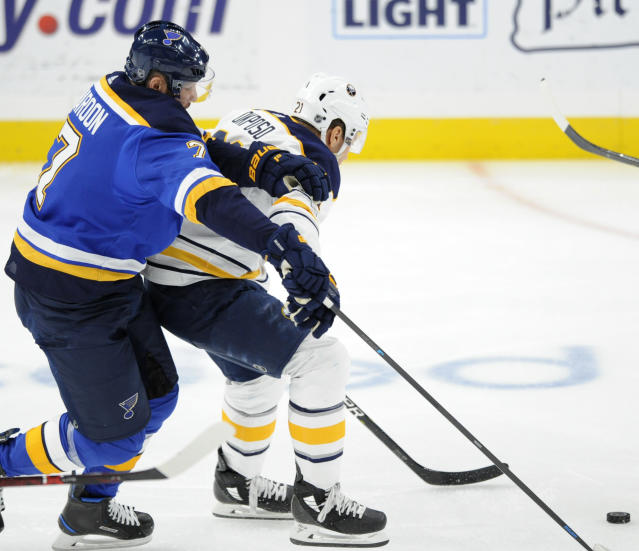 St. Louis Blues' Pat Maroon (7) battles for the puck with Buffalo Sabres' Kyle Okposo (21) during the first period of an NHL hockey game, Thursday, Dec. 27, 2018, in St. Louis. (AP Photo/Bill Boyce)