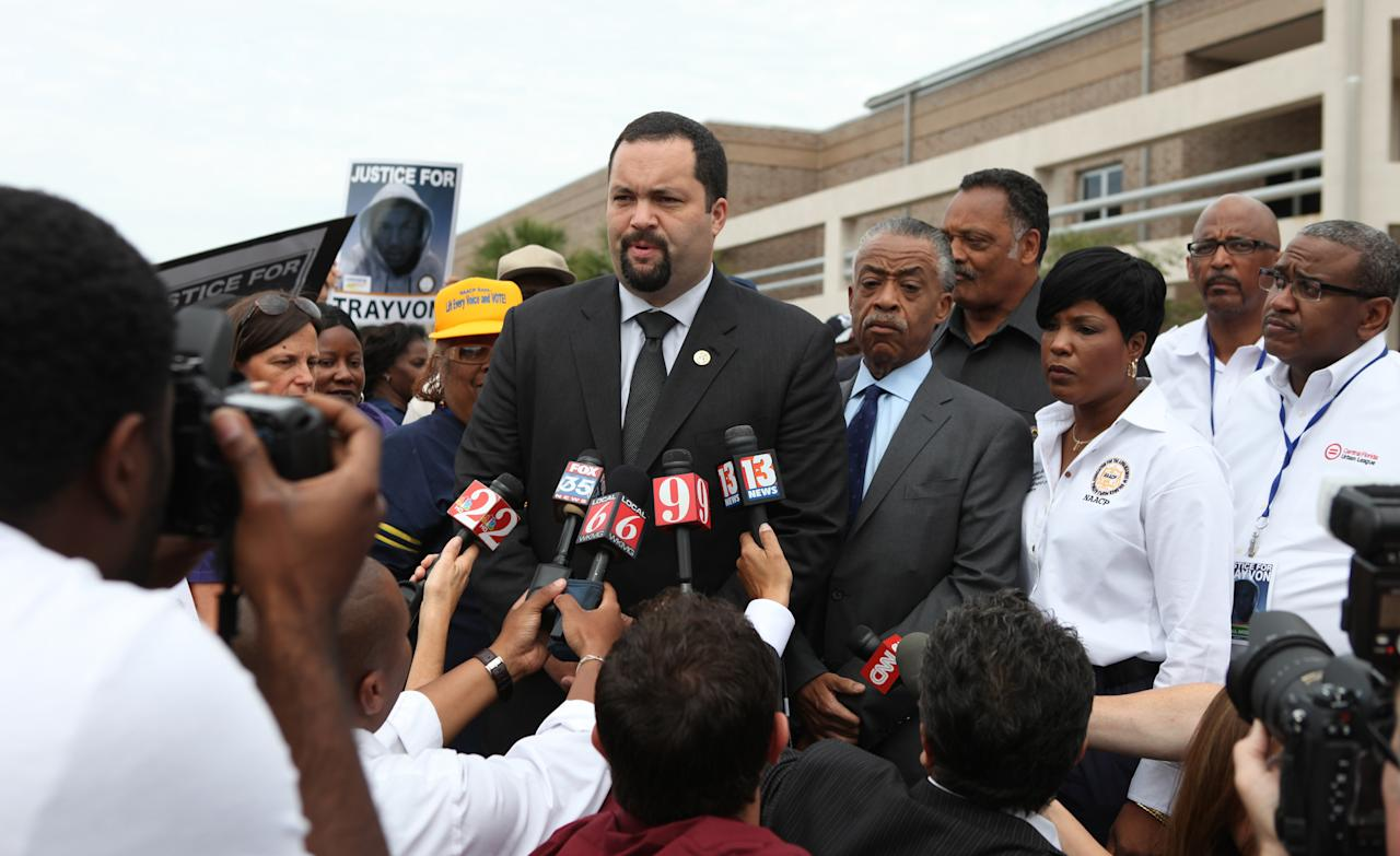 """Benjamin Jealous, President of the NAACP talks to the media as Rev. Al Sharpton and Rev. Jessie Jackson, back, listens before the march and rally for slain Florida teenager Trayvon Martin on Saturday, March 31, 2012 in Sanford, Fla. Protesters carried signs, chanted """"Justice for Trayvon,"""" and clutched the hands of their children while they walked from Crooms Academy of Information Technology, the county's first high school for black students, to the Sanford Police Department. The march was organized by the NAACP and was one of several taking place over the weekend. Martin was shot to death by 28-year-old George Zimmerman on Feb. 26 as he walked from back from a convenience store to his father's fiancée's home in a gated community outside Orlando. (AP Photo/Julie Fletcher)"""