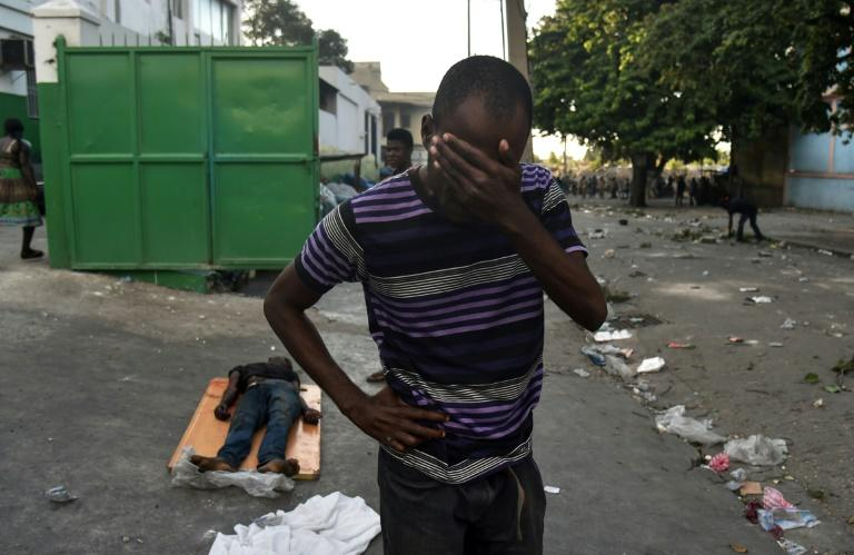 A man cries next to the body of a dead youth shot during clashes between Haitian police and demonstrators near the National Palace in Port-au-Prince, on February 9, 2019