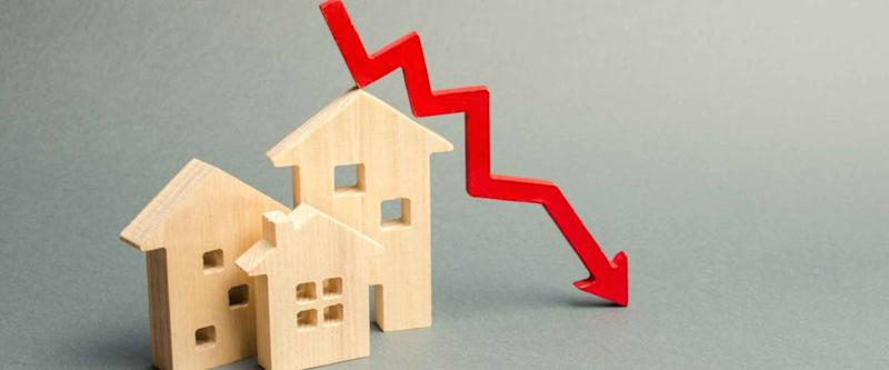 Miniature wooden houses and a red arrow down, signifying low mortgage rates