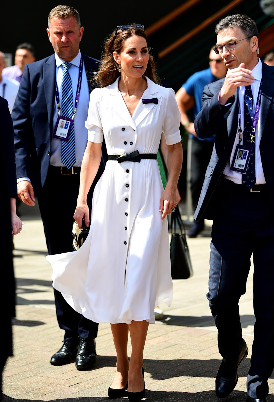 """Kate attended day two of Wimbledon, wearing a white<a href=""""https://www.suzannah.com/products/flippy-wiggle-dress"""" rel=""""nofollow noopener"""" target=""""_blank"""" data-ylk=""""slk:button-up dress by Suzannah"""" class=""""link rapid-noclick-resp""""> button-up dress by Suzannah</a>, with an Alexander McQueen bow detail belt and her Gianvito Rossi 'Piper' heels. A new raffia satchel by Alexander McQueen, her Catherine Zoraida earrings and a pair of Ray-Ban Wayfarers completed her courtside look. [Photo: PA]"""