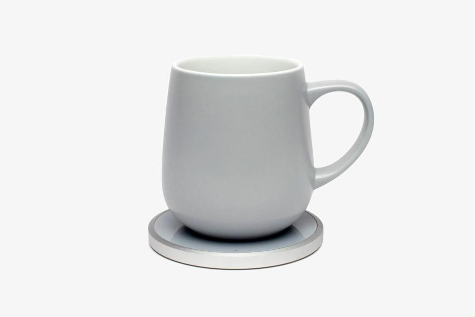 """Anyone who likes their coffee piping hot would be glad to get this Kopi warmer mug. Using magnetic induction to heat a metallic layering in the bottom of the mug, the Kopi keeps drinks warm all day, minus the burnt flavor some hot plates can add. While the set would likely be a welcome addition to any <a href=""""https://www.cntraveler.com/story/things-our-editors-swear-make-working-from-home-more-enjoyable?mbid=synd_yahoo_rss"""" rel=""""nofollow noopener"""" target=""""_blank"""" data-ylk=""""slk:home office set-up"""" class=""""link rapid-noclick-resp"""">home office set-up</a>, reviewers say the mug and warmer disc are also fairly packable. As a bonus, the bottom plate can double as a wireless phone charger—just make sure it cools first. $75, Nordstrom. <a href=""""https://www.nordstrom.com/s/kopi-mug-warmer-set/5593348"""" rel=""""nofollow noopener"""" target=""""_blank"""" data-ylk=""""slk:Get it now!"""" class=""""link rapid-noclick-resp"""">Get it now!</a>"""