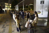 People wait in line at a taxi stand outside the Tokyo station when all the train services were suspended at the station in Tokyo on Thursday, Oct. 7, 2021, following an earthquake. Some train services resumed later. (AP Photo/Hiro Komae)